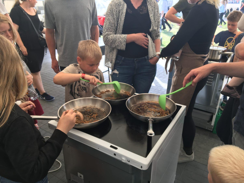 Der er gang i teltet på Food Festival, hvor melormene nu er kommet i panderne og sprutter og vrider sig i varmen. Om 8-10 minutter er de færdige og klar til krydderierne. Foto: Josefine Aude Raas.